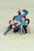 Family in blue lying on the sand — Stock Photo