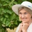 Pretty elderly woman in the park — Stock Photo