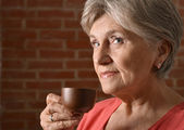 Senior woman with cup — Stockfoto