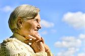 Happy elderly woman posing against the sky — Stock Photo