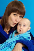 Mom holding her baby on a blue — Stock Photo