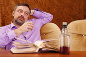 Cute man with whiskey reading — Stock Photo
