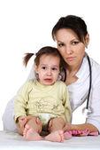 Bella e brava infermiera con una ragazza seduta — Foto Stock