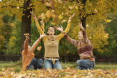 Mom and her children throwing autumn leaves — Stock Photo
