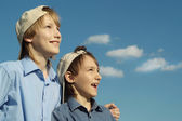 Boys in a caps under a blue sky — Stock Photo