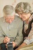 Senior couple working on personal digital assistant — Stock Photo