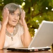 Older woman with computer outdoors — Stock Photo