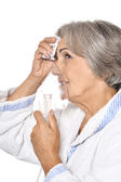 Sick elderly lady with inhaler — Stock Photo