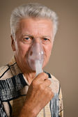 Elder man making inhalation — Stock Photo