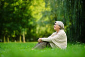 Cute old woman in the middle of the lawn — Stock Photo