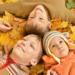 Family of three lying on yellow leaves — Stock Photo