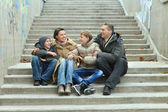 Family of four sitting on stairs — Stock Photo