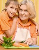 Mutlu yaşlı kadın ve çocuk mutfakta turuncu — Stok fotoğraf