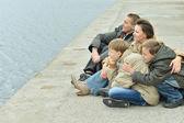 一家四口坐在河堤 — 图库照片
