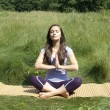 Happy cute girl meditates in a summer park — Stock Photo