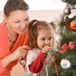 Lovely mother decorating christmas tree with daughter — Stock fotografie