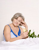 Beautiful older woman resting in the bedroom after a hard working week — Stock Photo