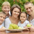 Family eating fruits outdoors — Stock Photo