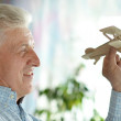 Senior man with wooden plane — Stock Photo