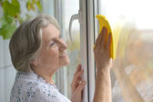 Senior woman cleaning window — Stockfoto