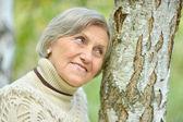 Senior woman by the tree — Stock Photo