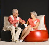 Elderly couple resting on armchairs — Stock Photo