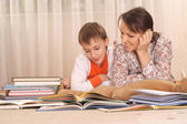 Beautiful charming mother with her son reading a book — ストック写真