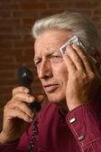 Sick mature man speaking on phone on a brick background — Stock Photo