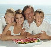 Hermosa familia comiendo sandía — Foto de Stock