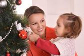 Belle mère décorant le sapin de noël avec fille — Photo