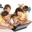 Cute family with laptop on a floor — Stock Photo