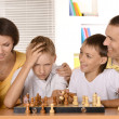 Happy family playing chess sitting at table — Stock Photo #38483103