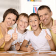 Happy family drawing at the table together and showing thumb up — Stock Photo
