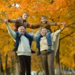Happy senior couple in autumn park with grandchildrens — Stock Photo