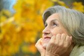 Portrait of thinking senior woman in autumn park — Stock Photo