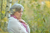 Portrait of sad elderly woma standing by a tree — Stock Photo