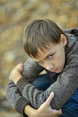 Portrait of a sad little boy outdoors in autumn — Stock Photo