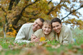 Happy family in park lying on yellow leaves — Stock Photo