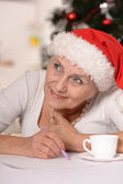 Happy elderly woman in santa hat writting a letter — Stock Photo