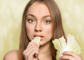 Beautiful young girl eating cabbage — Stock Photo