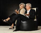 Elderly couple sitting on armchairs — Stok fotoğraf