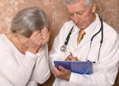 Sad senior woman with doctor — Stockfoto
