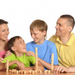 Stock Photo: Happy family playing lotto
