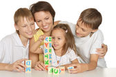 Mother and her kids playing with cubes isolated on white — Stock Photo