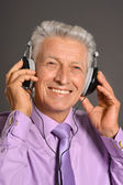 Elderly man listen to music in headphones — Stock Photo