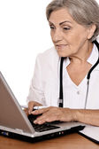 Woman doctor sitting with laptop — Stock Photo