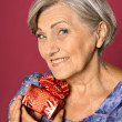 Senior woman with gift box — Stock Photo