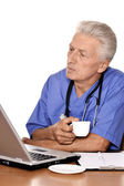 Elderly doc with a laptop — Stock Photo