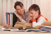 Beautiful charming mother with her son reading a book — Stockfoto