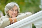 Portrait of happy eldery woman in park — Stock Photo
